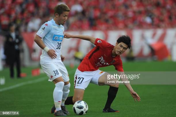 Daiki Soga of Consadole Sapporo and Daiki Hashioka of Urawa Red Diamonds compete for the ball during the JLeague J1 match between Urawa Red Diamonds...