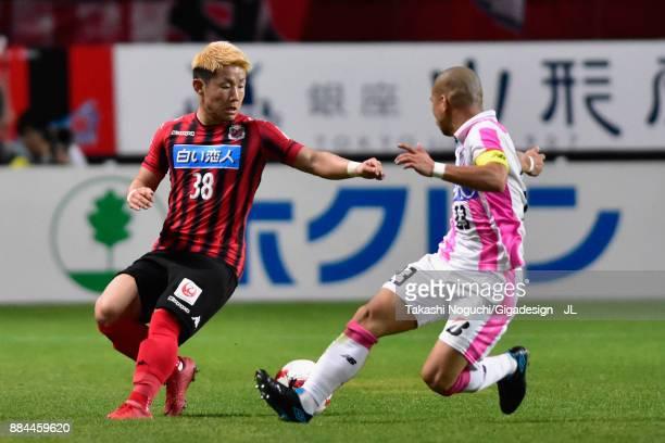 Daiki Suga of Consadole Sapporo and Yutaka Yoshida of Sagan Tosu compete for the ball during the JLeague J1 match between Consadole Sapporo and Sagan...