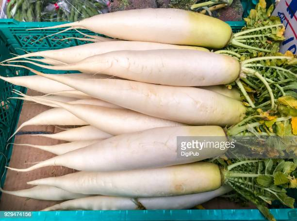 daikon radish piled for sale - dikon radish stock photos and pictures