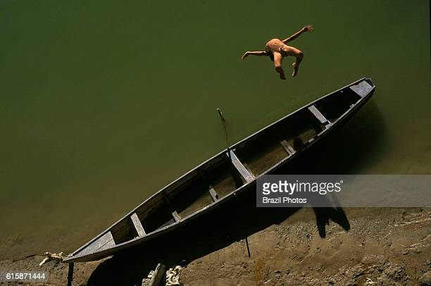Daily life at the border of Sao Francisco river at Malhada city in Bahia State northeastern Brazil naked 8years old boy jumps in river from canoe