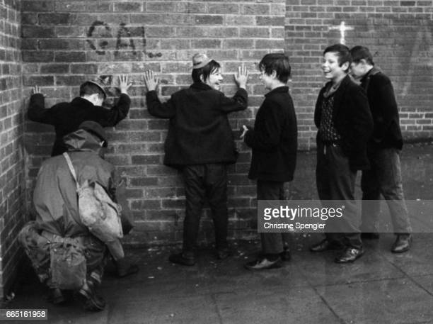 Daily life goes on in Belfast, even with a constant military reminder of the anti-English struggle, as five boys dressed for carnival celebrations are frisked by a soldier against a wall.