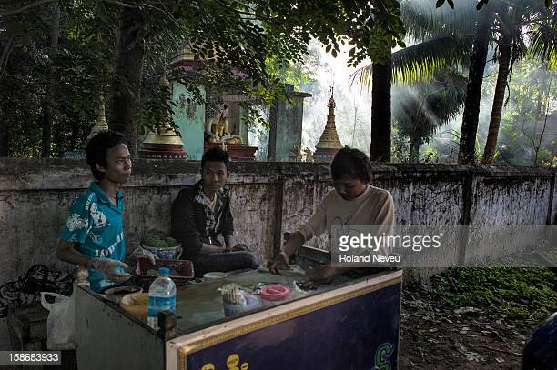 Daily life in Mawlamyine a group of young men chat and make pods of betel for chewing on front of sun filled pagoda