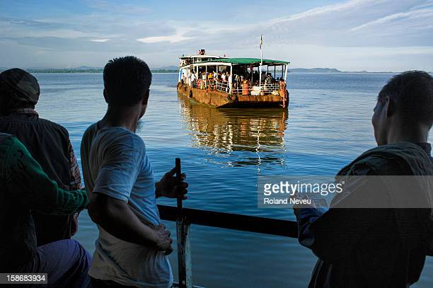 Daily life in Mawlamyine an old boat full of passenger is docking at a pier near the Central market