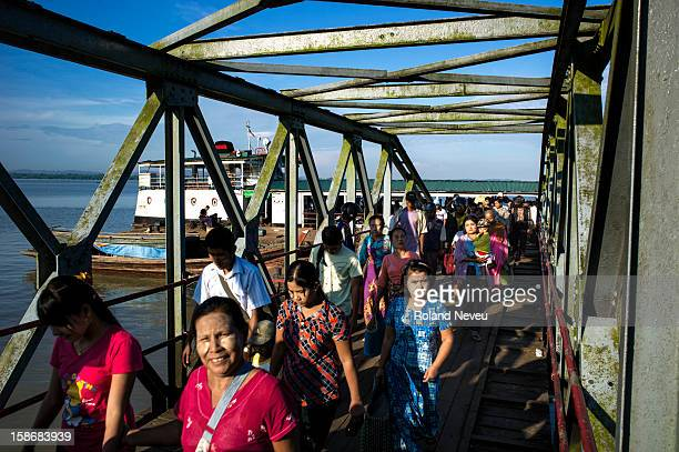 Daily life in Mawlamyine passengers getting off an old boat docked at a pier near the Central market
