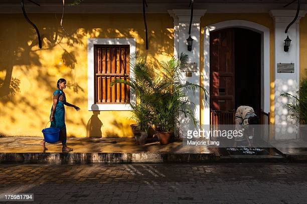 Daily life scene in light and shadows with a woman carrying a bucket and another woman drawing a kollam in front of the door of a colorful yellow...