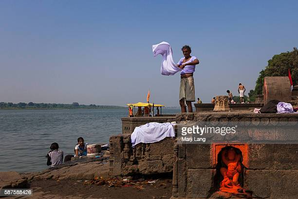 Daily life scene of people doing their laundry and drying clothes by the Narmada river on the ghats of Maheshwar in Madhya Pradesh India