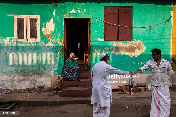 CONTENT] Daily life scene with two men interacting and a woman watching from her doorstep in a colorful street of Mattancherry Kochi Kerala India