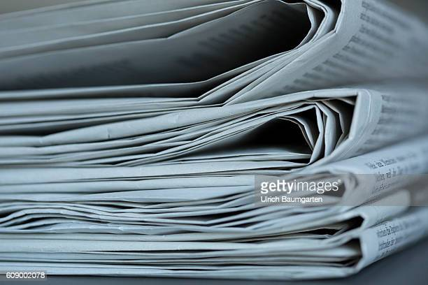 Daily newspapers stacked one on top