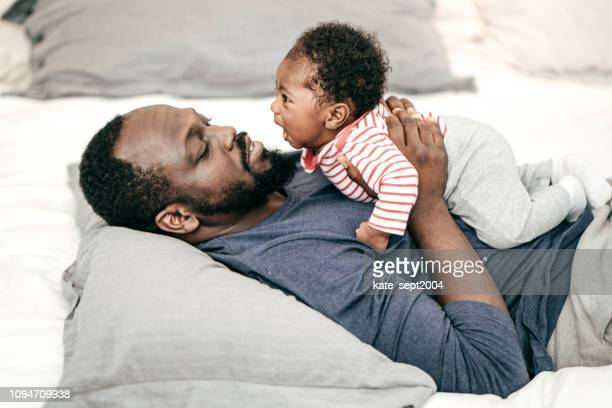 daily parents activity - black man holding baby stock photos and pictures