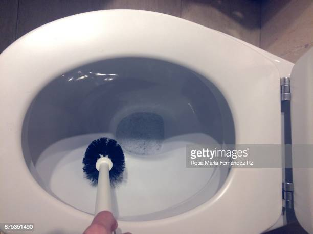 Daily perspective: Cropped hand of person cleaning toilet bowl. Top view.