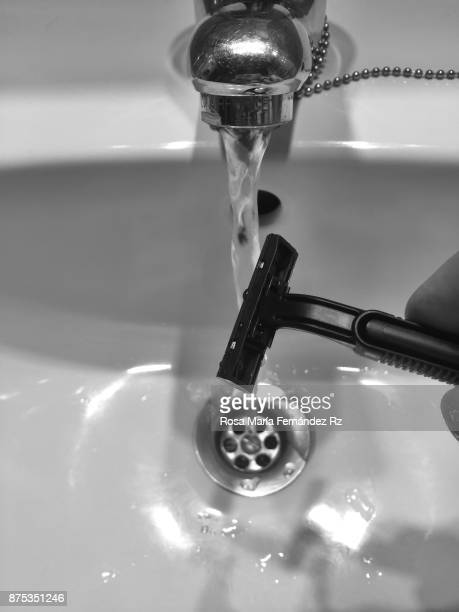 Daily perspective: Cropped hand washing a razor in the sink