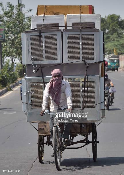 A daily wage labourer transports air coolers after government eased lockdown restriction at Rani Jhansi Road on May 20 2020 in New Delhi India