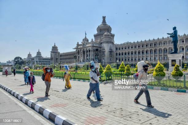 Daily wage labourers and their families carrying their belongings walk past the Vidhana Soudha building as they leave the city for their hometown...