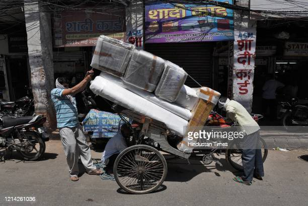 Daily wage labourers load the goods on the cart after government eased lockdown restriction at Nai Sadak on May 20 2020 in New Delhi India