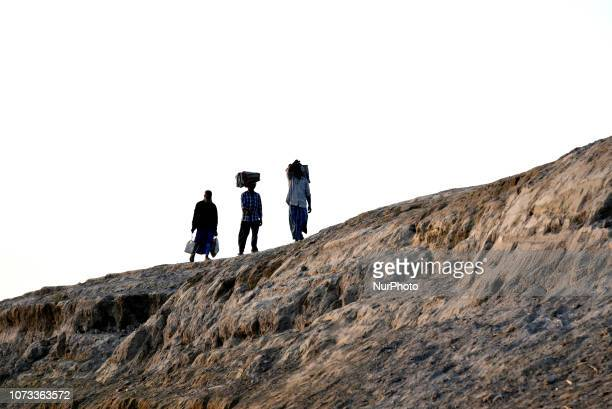 Daily wagers returning home after work during sunset walking over soil eroded banks of Brahmaputra river in Bahari village of Barpeta Assam India on...