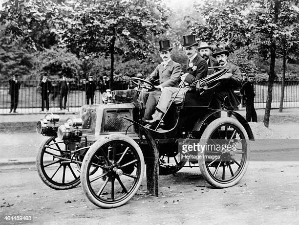 Daimler 1899 The two men in front are wearing top hats The front seat passenger also wears a flower in his lapel and carries a cane