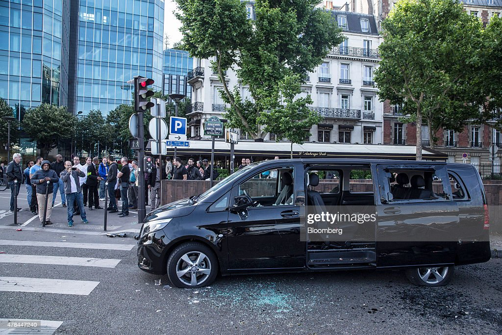 A Daimler AG Mercedes-Benz people carrier sits badly damaged after being targeted by taxi drivers during a protest against Uber Technologies Inc.'s car sharing service in Paris, France, on Thursday, June 25, 2015. French taxi drivers are on indefinite nationwide strike as they demand a government crackdown on what they say is Uber's use of unlicensed chauffeurs for its UberPop service. Photographer Balint Porneczi/Bloomberg via Getty Images