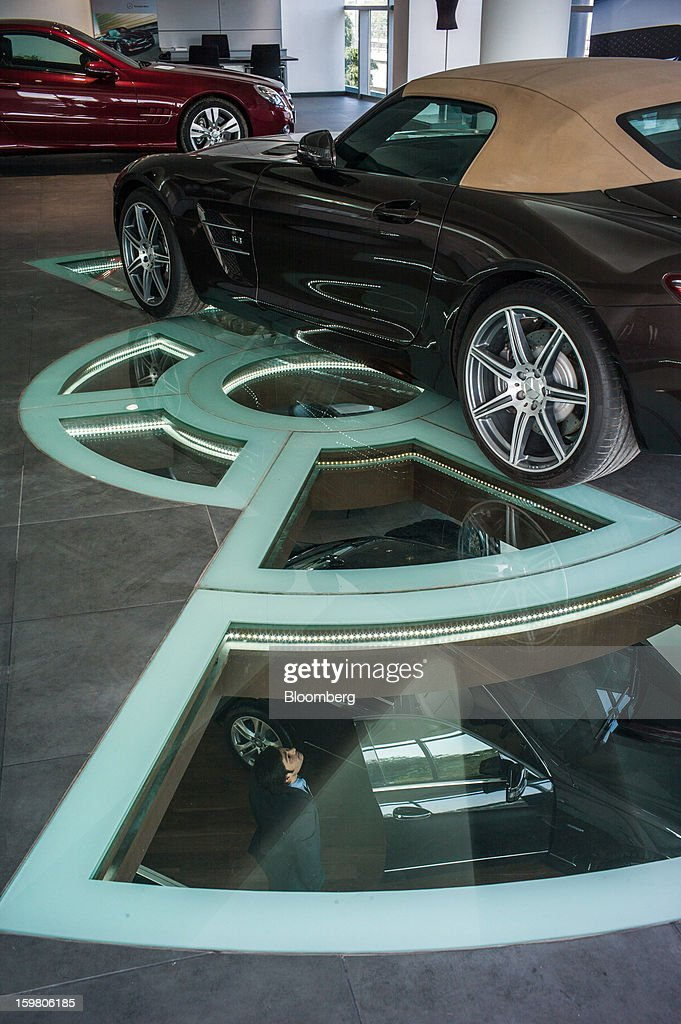 A Daimler AG Mercedes-Benz SLS AMG Roadster vehicle sits on display as a T&T Motors Ltd. sales assistant is viewed looking up through a glass floor inside the company's newly opened Mercedes-Benz India flagship dealership in New Delhi, India, on Saturday, Jan. 19, 2013. The Indian Finance Ministry projects Asia's third-largest economy will expand as little as 5.7 percent in the 12 months to March 31, which would be the weakest pace in a decade. Photographer: Sanjit Das/Bloomberg via Getty Images