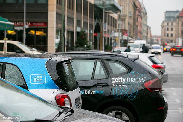 A Daimler AG Smart ForTwo Car2Go carsharing automobile left sits parked beside a BMW X1 DriveNow car manufactured by Bayerische Motoren Werke AG in...