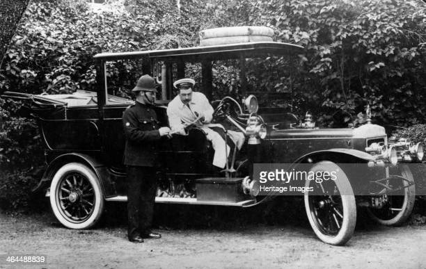 Daimler, . WL Woodbine, the chauffeur of the Earl of Sandwich, is showing papers to a policeman.