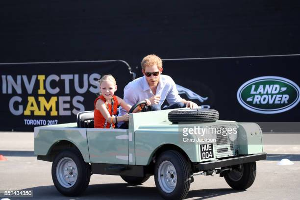 Daimy Gommers drives the car as Prince Harry rides beside her as he visits the Distillery District of the city for the Jaguar Land Rover driving...