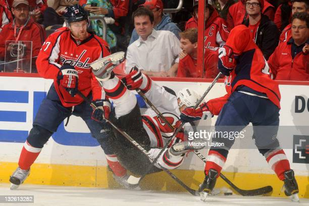 Dainius Zubrus of the New Jersey Devils gets hit against the wall by Karl Alzner and another player of the Washington Capitals during a NHL hockey...
