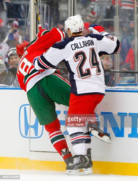 Dainius Zubrus of the New Jersey Devils is checked from behind by Ryan Callahan of the New York Rangers during the 2014 NHL Stadium Series NY on...