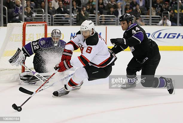Dainius Zubrus of the New Jersey Devils is pursued by Davis Drewiske of the Los Angeles Kings for the puck as goaltender Jonathan Quick defends in...