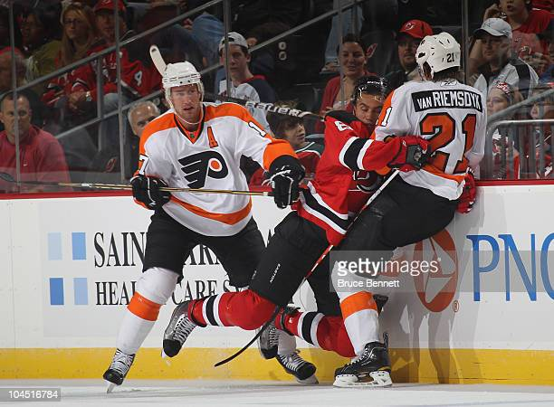Dainius Zubrus of the New Jersey Devils is sandwiched between Jeff Carter and James van Riemsdyk of the Philadelphia Flyers at the Prudential Center...