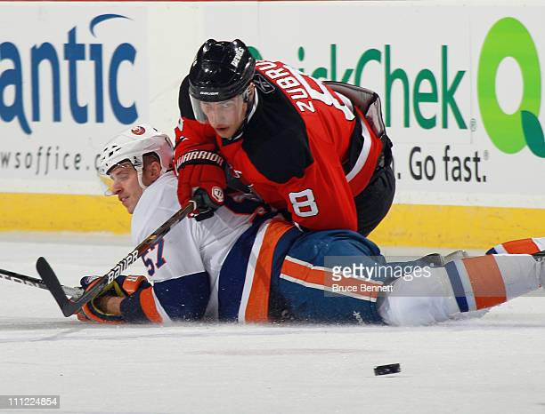 Dainius Zubrus of the New Jersey Devils trips up Blake Comeau of the New York Islanders at the Prudential Center on March 30 2011 in Newark New Jersey