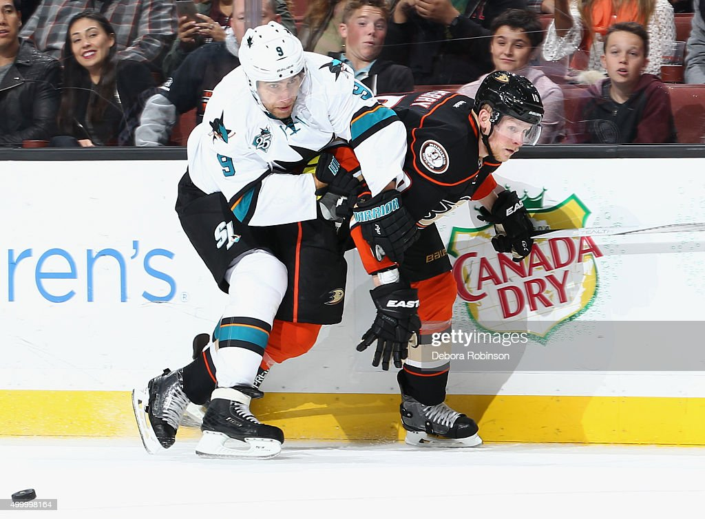 Dainius Zubrus #9 of the San Jose Sharks and Corey Perry #10 of the Anaheim Ducks battle for the puck on December 4, 2015 at Honda Center in Anaheim, California.