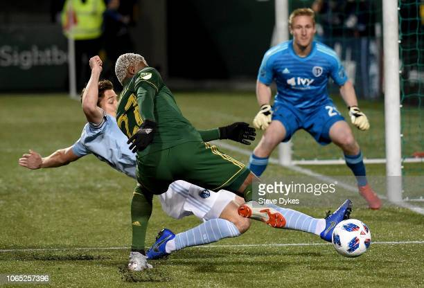 Dairon Asprilla of Portland Timbers tries to get aroun Matt Besler of Sporting Kansas City as Tim Melia waits in goal during the first half of the...