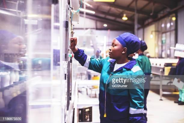 operador de linha de produção fêmea de fábrica de laticínios no trabalho - 1 de maio - fotografias e filmes do acervo