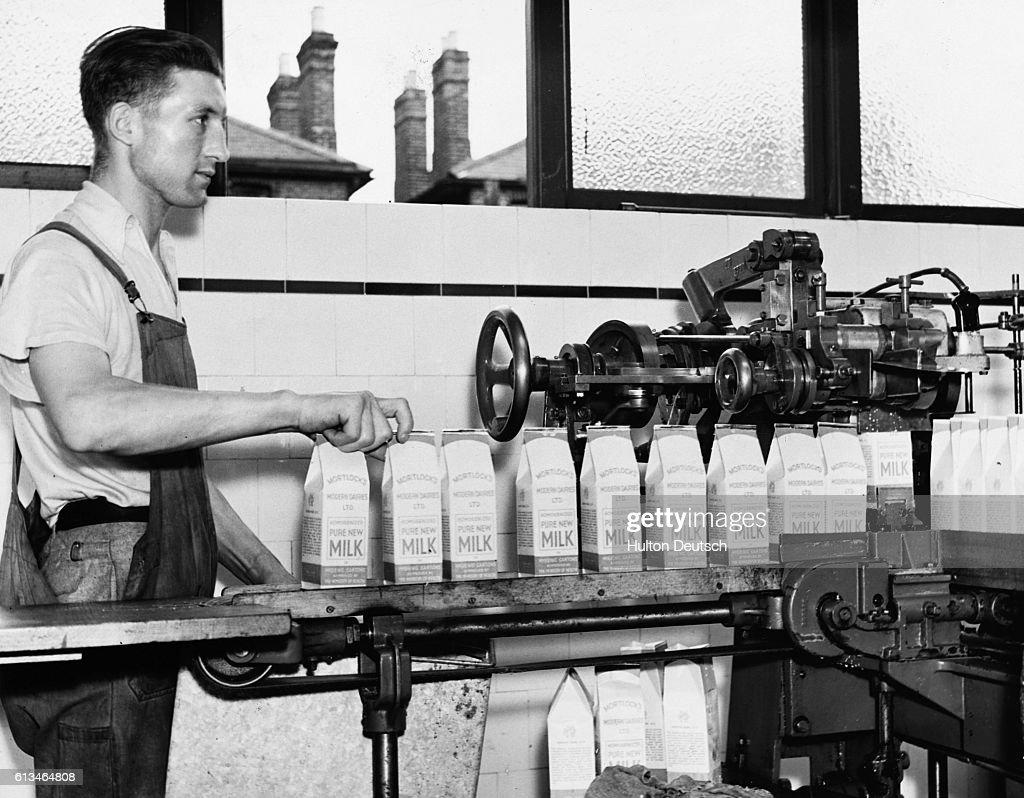 Man Working Milk Carton Machine : News Photo