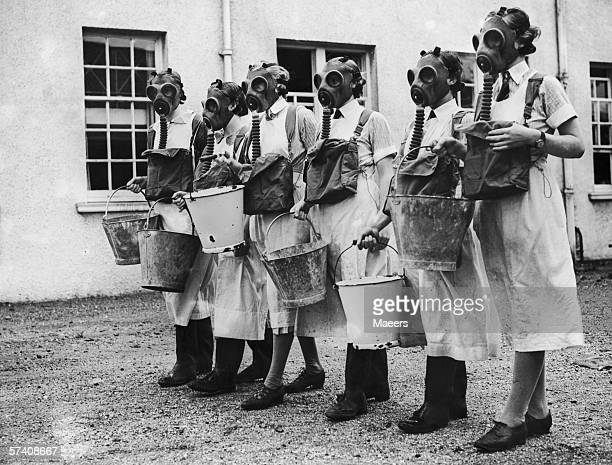 Dairy workers at the Monmouthshire Institute of Agriculture in Usk carry out a gas mask drill at the institute's new ARP unit 30th July 1938