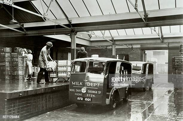 Dairy workers load milk bottles onto an electric vehicle or milk float for local delivery in Blackpool