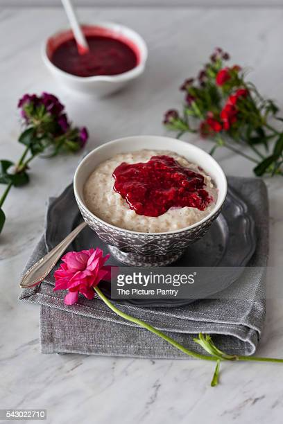 Dairy-free rice pudding cooked in almond milk in a bowl with raspberry sauce