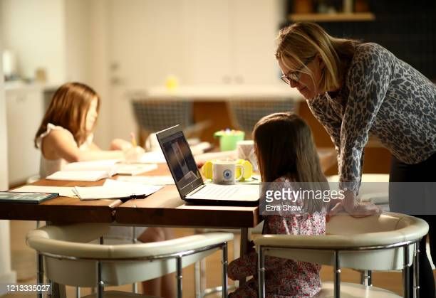 Daisley Kramer helps her kindergarten daughter Meg with schoolwork at home on March 18 2020 in San Anselmo California Fourth grader Lucy Kramer is...