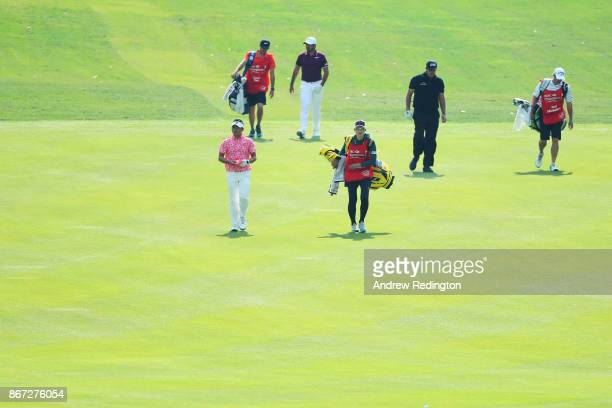 Daisuke Kataoka of Japan Phil Mickelson of the United States and Jason Day of Australia walk on the first hole during the third round of the WGC HSBC...