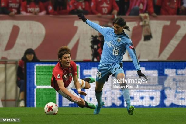 Daisuke Kikuchi of Urawa Red Diamonds and Elsinho of Kawasaki Frontale compete for the ball during the J.League J1 match between Urawa Red Diamonds...