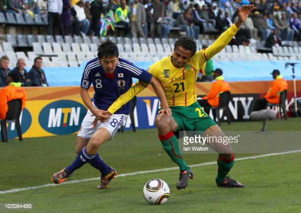Daisuke Matsui of Japan and Joel Matip of Cameroon tussle for the ball during the 2010 FIFA World Cup South Africa Group E match between Japan and...