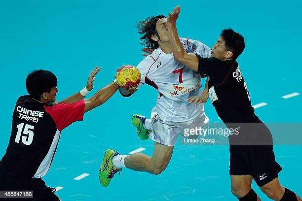 Daisuke Miyazaki of Japan is defended by ChiaWei Weng and HsienMing Hsu of Chinese Taibei during the Handball Men's Group D match between Chinese...
