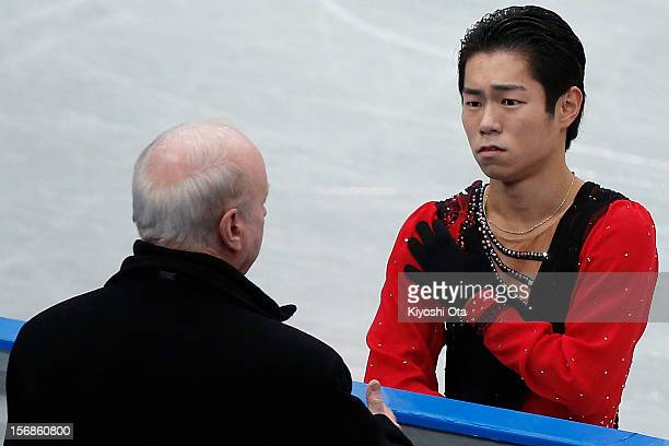 Daisuke Murakami of Japan speaks to his coach Frank Carroll as he holds his injured shoulder in the Men Short Program during day one of the ISU Grand...