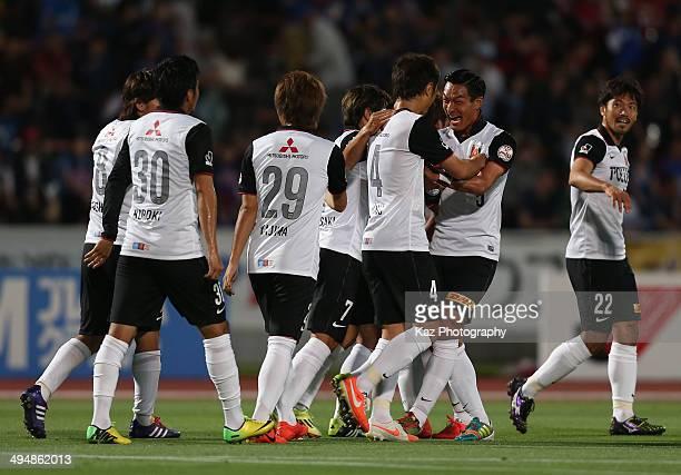 Daisuke Nasu of Urawa Red Diamonds celebrates scoring his team's first goal with his teammates during the J.League Yamazaki Nabisco Cup Group B match...