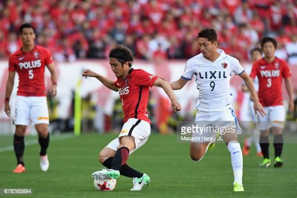 Daisuke Nasu of Urawa Red Diamonds controls the ball under pressure of Yuma Suzuki of Kashima Antlers during the JLeague J1 match between Urawa Red...