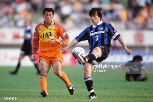 Daisuke Saito of Gamba Osaka and Kenta Hasegawa of Shimizu S-Pulse compete for the ball during the J.League first stage match between Gamba Osaka and...