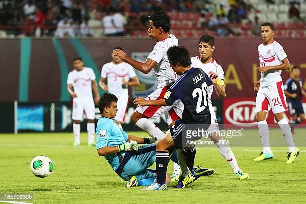 Daisuke Sakai of Japan scores his team's first goal against goalkeeper Hamza Ben Chrifia of Tunisia during the FIFA U17 World Cup UAE 2013 Group D...