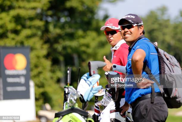 Daisuke Shindo caddie for Hideki Matsuyama of Japan gives a thumbs up with trainer Mitsuteru Iida on the practice green during the final round of the...