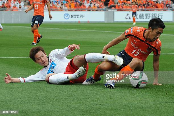 Daisuke Watabe of Omiya Ardija and Kazuki Kushibiki of Consadole Sapporo compete for the ball during the J.League second division match between Omiya...