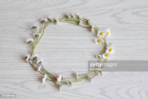 Daisy flowers in a circle crown on table top
